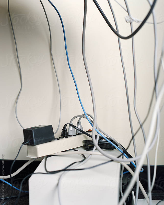 Various electrical cables and outlets beneath messy office desk by Paul Edmondson for Stocksy United