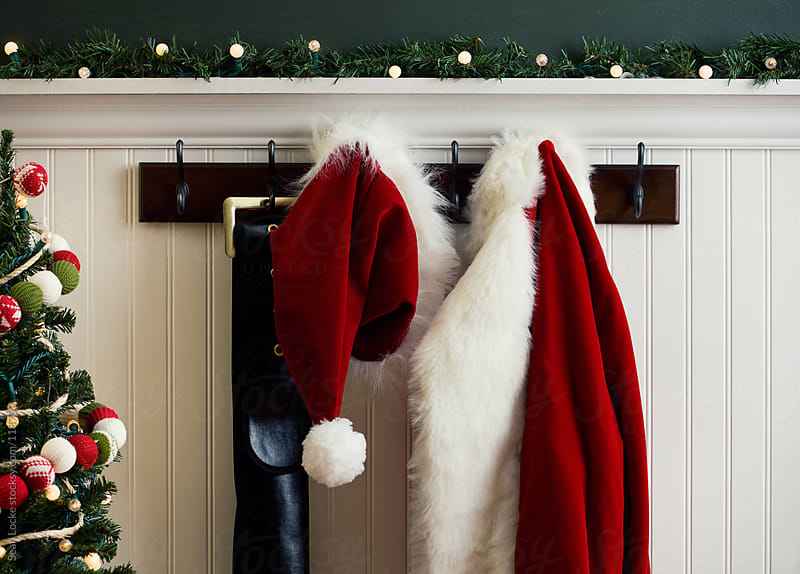 Christmas: Santa Coat and Hat Hanging Next to Christmas Tree by Sean Locke for Stocksy United