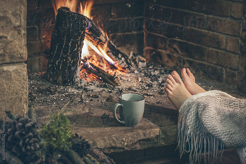 Woman's feet with blanket and hot cup of tea in front fireplace. by BONNINSTUDIO for Stocksy United