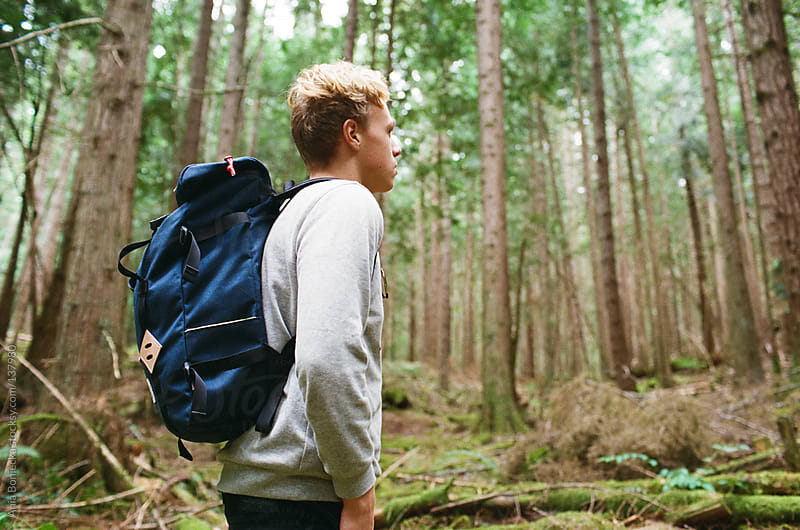 A young man hikin in a forest by Ania Boniecka for Stocksy United