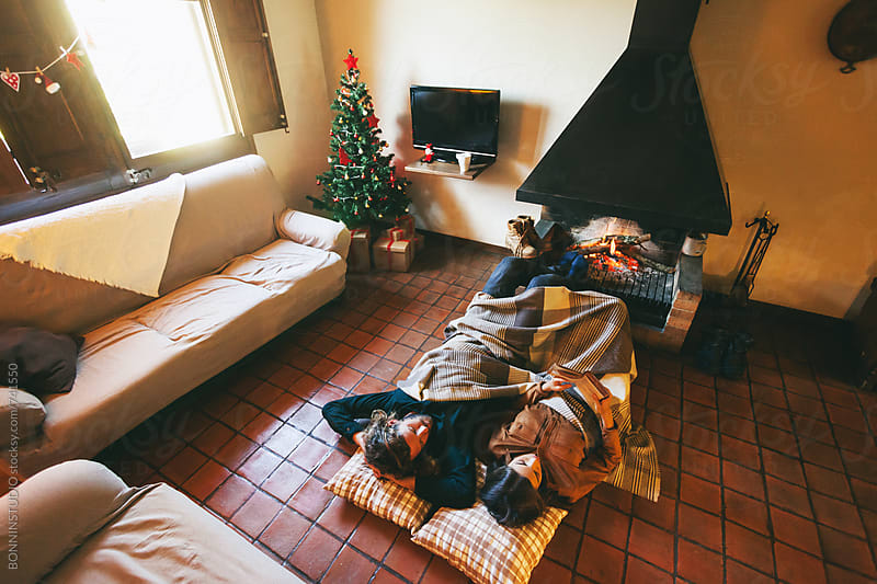 Overhead of a couple resting by the fireplace on winter. by BONNINSTUDIO for Stocksy United