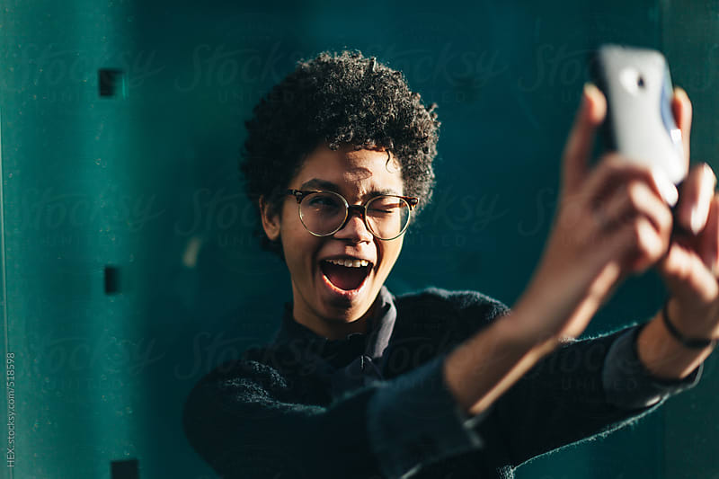 Funny Black Woman Taking Self Portrait with Mobile Phone by HEX. for Stocksy United