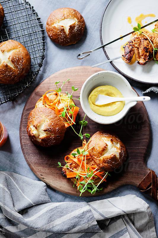 Grilled chicken sandwiches on pretzel buns by Ellie Baygulov for Stocksy United