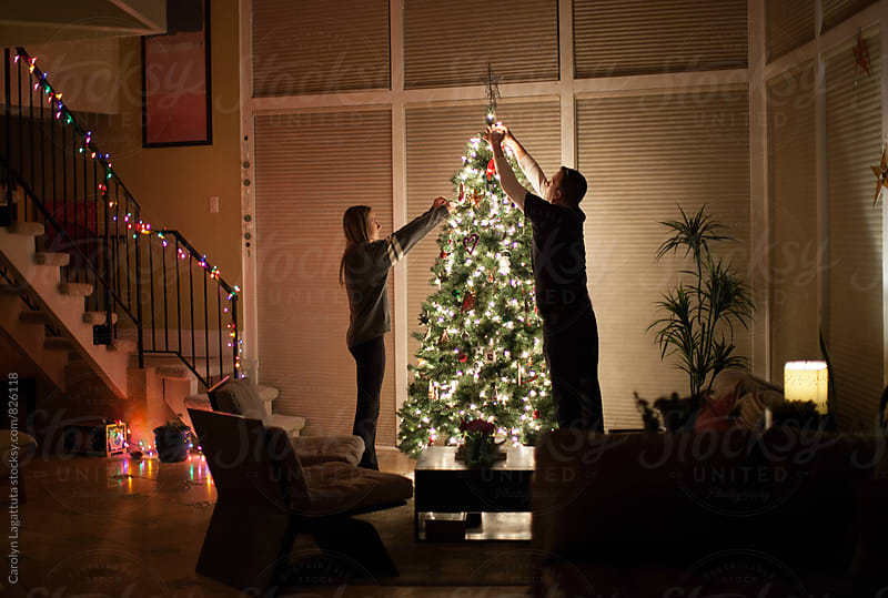 Father and daughter decorating the Christmas tree at night by Carolyn Lagattuta for Stocksy United