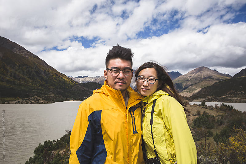 young couple take picture by the lakeside by zheng long for Stocksy United