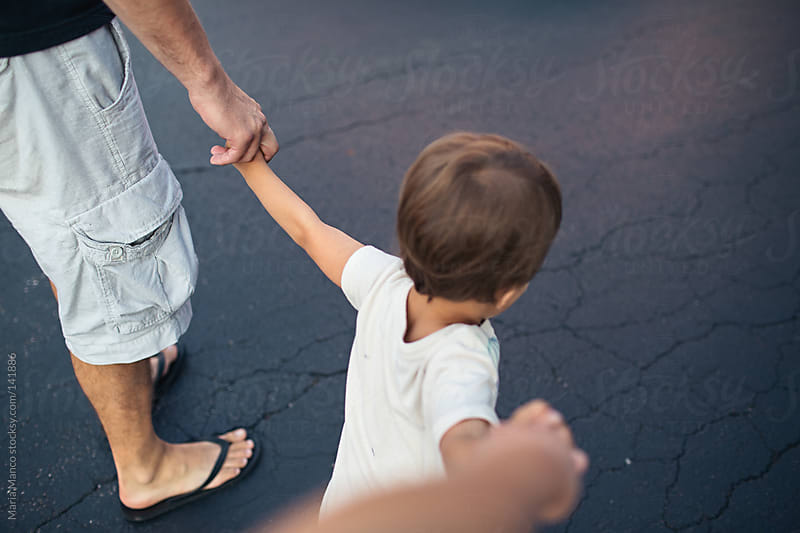 child walks holding parents hands by Maria Manco for Stocksy United