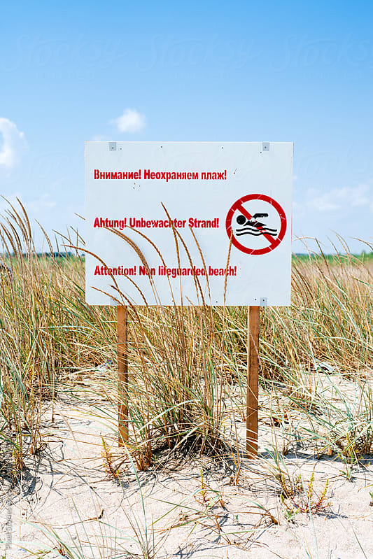 Non-lifeguarded beach sign against sparsely populated beach by Pixel Stories for Stocksy United