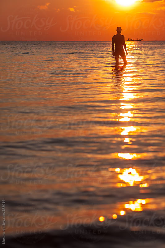 Silhouette of a Man Standing in Shallow Water by Mosuno for Stocksy United