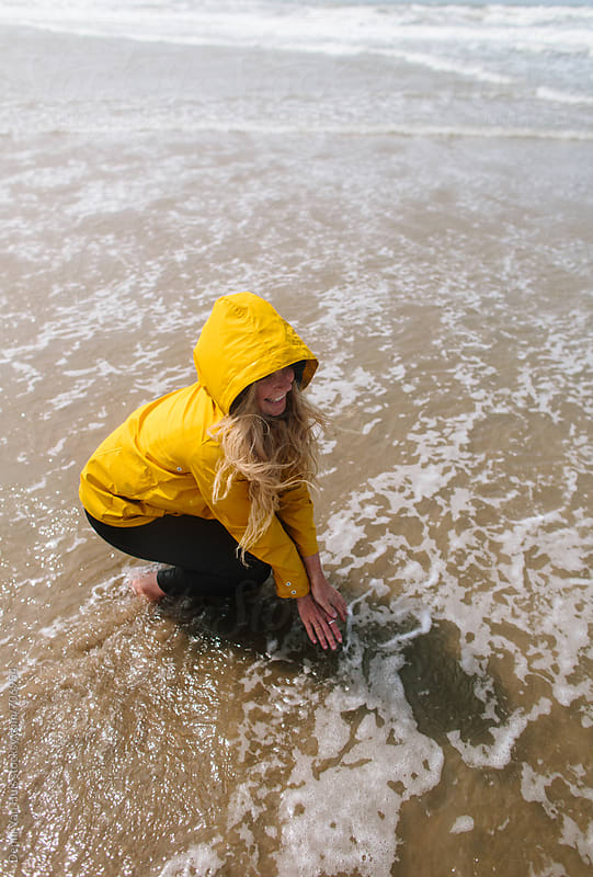 Woman touches water on a windy beach wearing a yellow raincoat by Denni Van Huis for Stocksy United