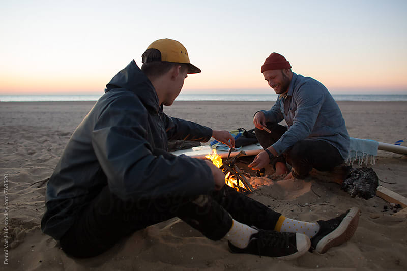 Cold night. Two Friends making a bonfire on the beach during sunset by Denni Van Huis for Stocksy United