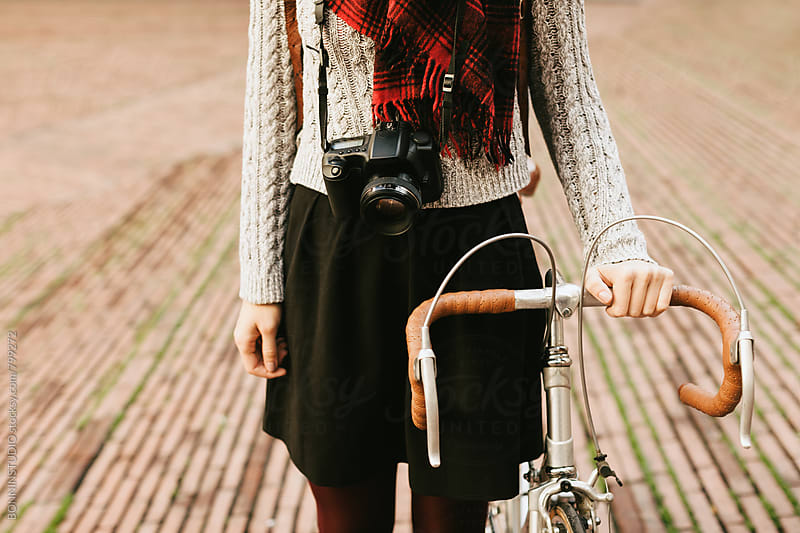 Closeup of a tourist female standing with her vintage bicycle on the street. by BONNINSTUDIO for Stocksy United