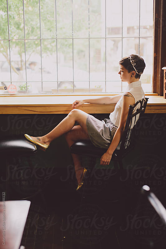 Girl sitting at a wine bar by a window by Gabrielle Lutze for Stocksy United