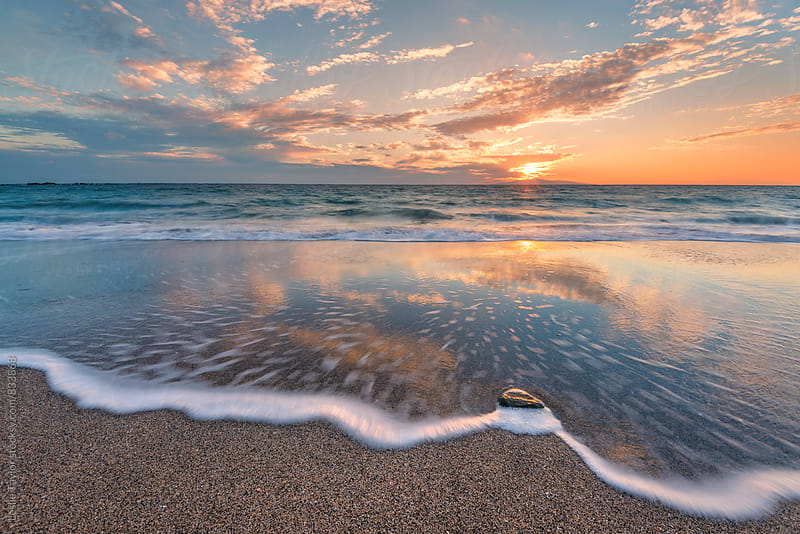 A Gentle Wave On A Beach At Sunset by Leslie Taylor for Stocksy United