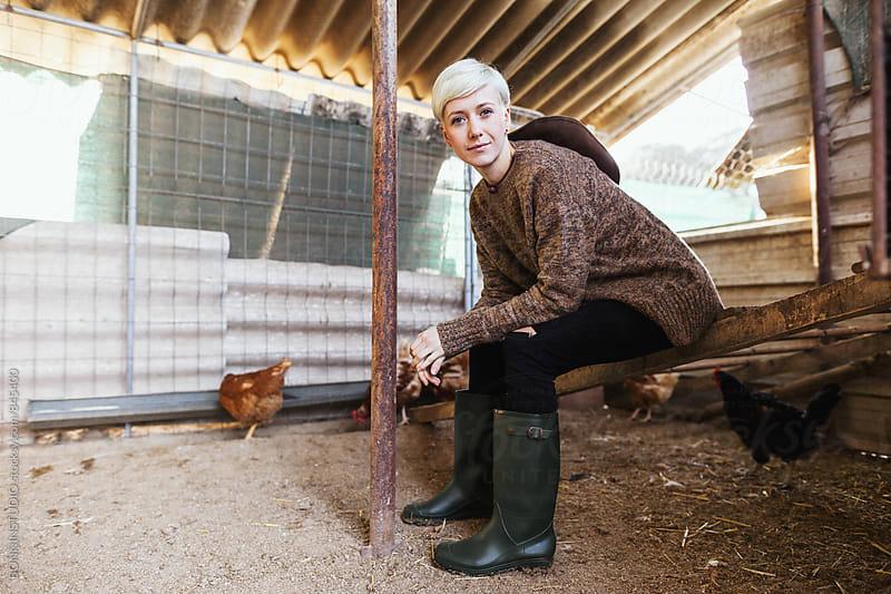 Woman farmer resting in a henhouse. by BONNINSTUDIO for Stocksy United