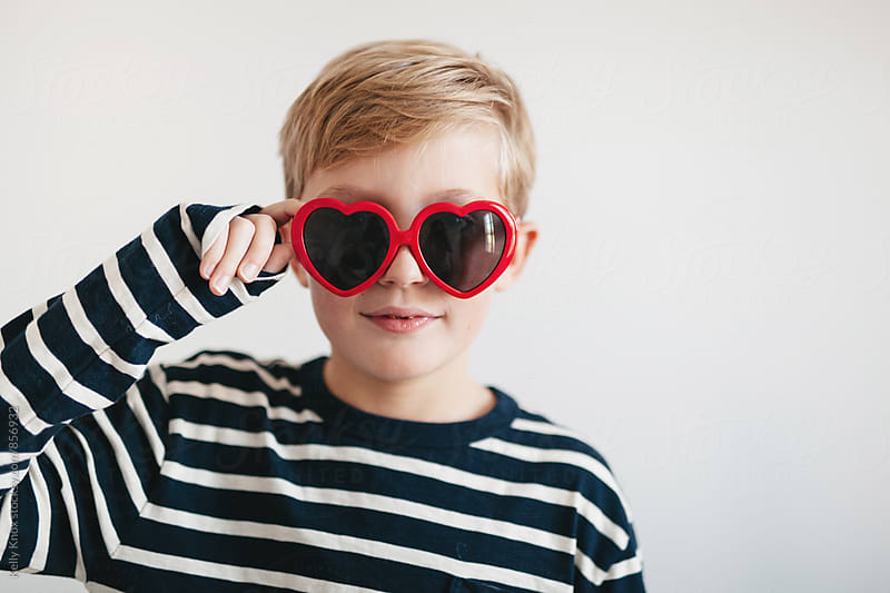 cute boy looking through heart shaped sunglasses by Kelly Knox for Stocksy United