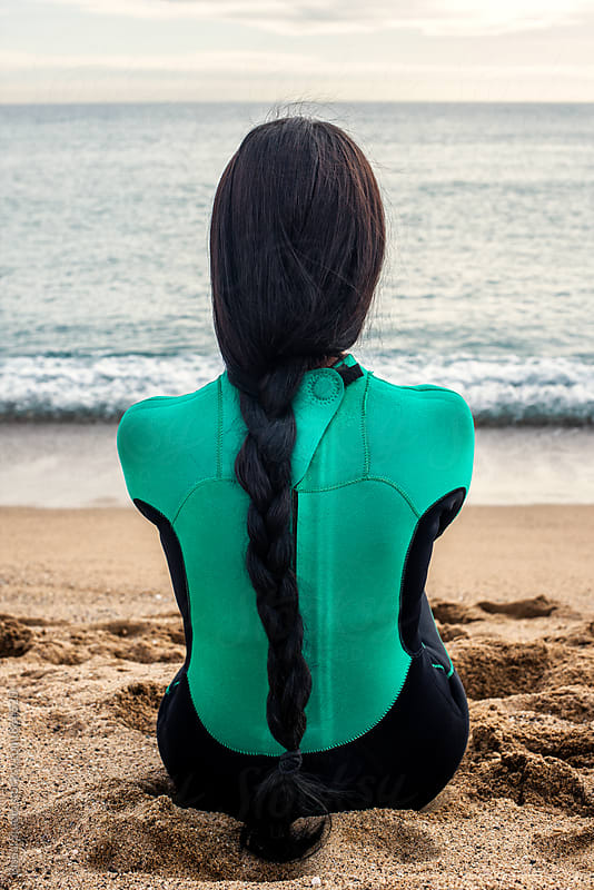 Back of a surfer woman with a long braid gazing at the sea, Barcelona  by Bisual Studio for Stocksy United
