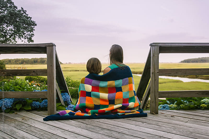 Boy With Son  wrapped in Blanket on Porch by Raymond Forbes LLC for Stocksy United
