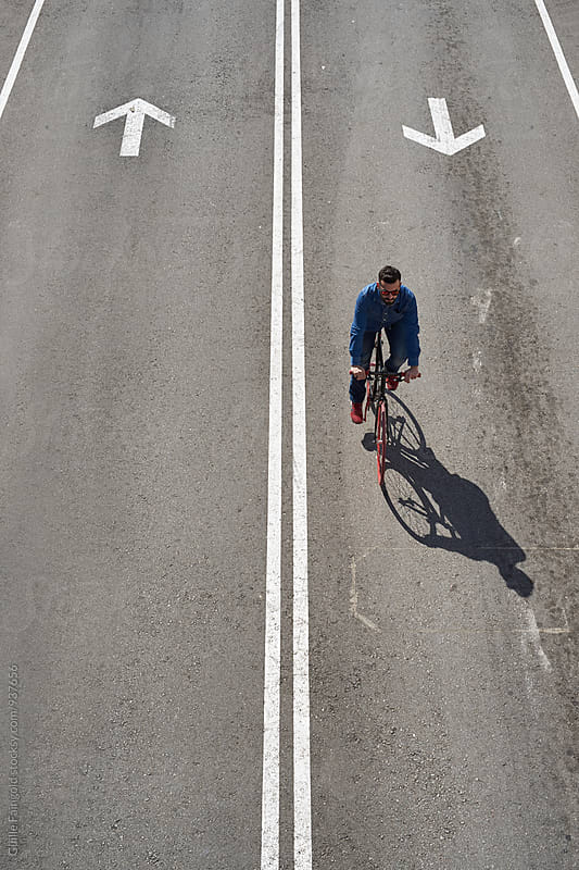 From above, young man ride his bicycle on roadway by Guille Faingold for Stocksy United