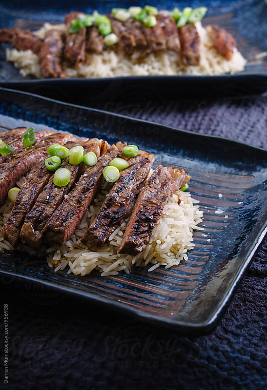 Vietnamese style sirloin beef steak with rice and spring onions. by Darren Muir for Stocksy United