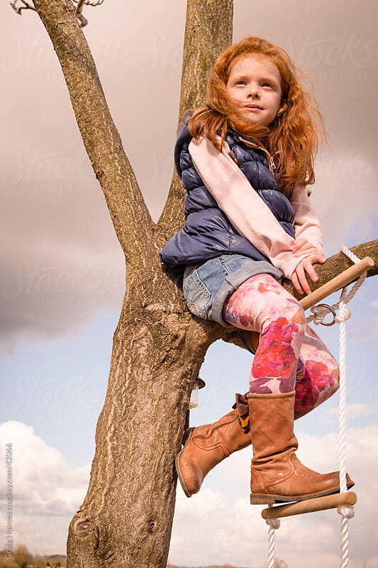 Girl climbing tree in countryside by Craig Holmes for Stocksy United
