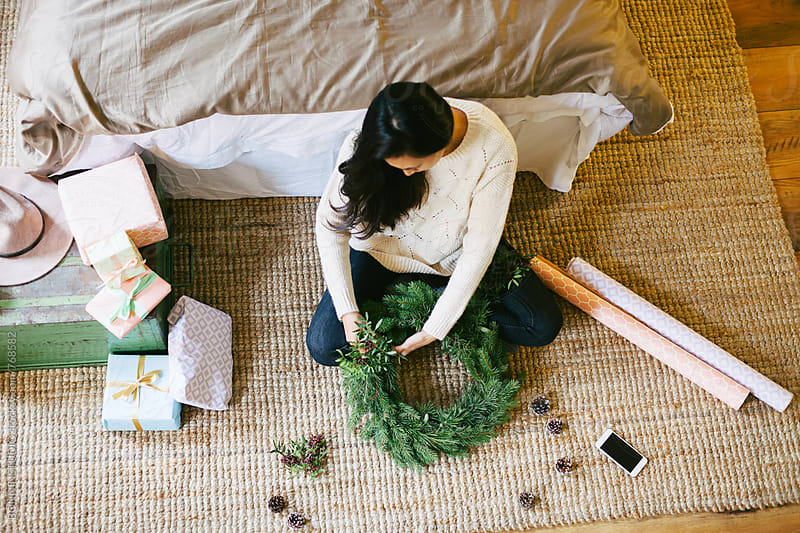 Young woman making a Christmas wreath at home. by BONNINSTUDIO for Stocksy United