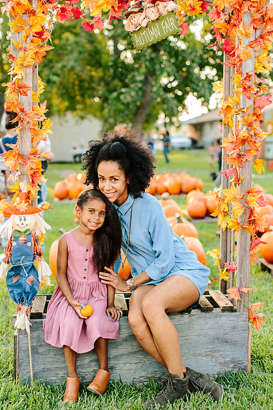 A mother & daugther sitting under a autumn leaf photo booth  by Kristen Curette Hines for Stocksy United
