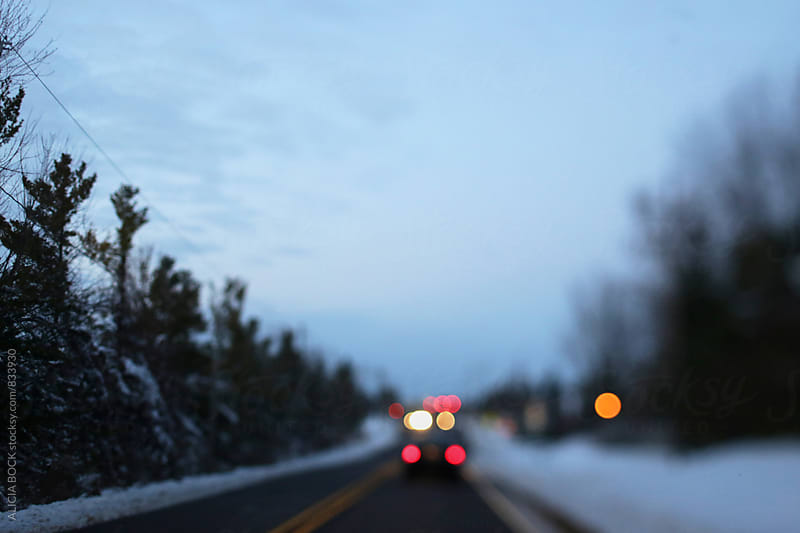 Car Lights On A Snowy Winter Road by ALICIA BOCK for Stocksy United