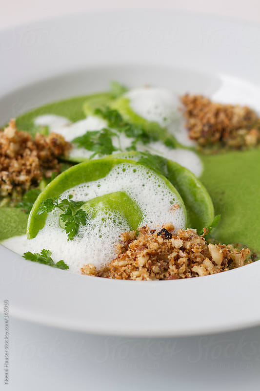 Close up of green ravioli with foam and crumble in sauce by Noemi Hauser for Stocksy United