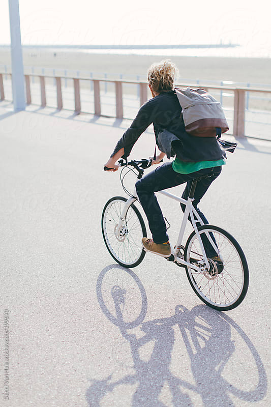 Man riding bike over a boulevard along the beach. by Denni Van Huis for Stocksy United