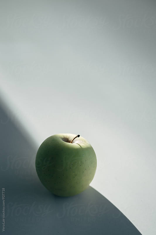 Green apple in the shade by Vera Lair for Stocksy United