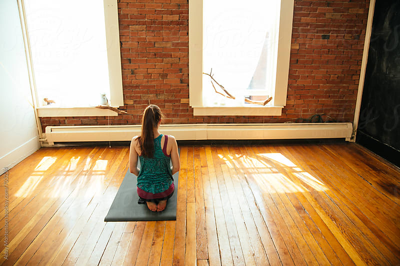 Back of Girl sitting in Yoga studio  by Abby Mortenson for Stocksy United