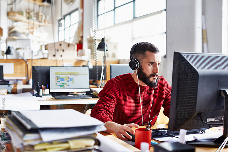 Businessman Wearing Headphones While Using Computer In Office by ALTO IMAGES for Stocksy United