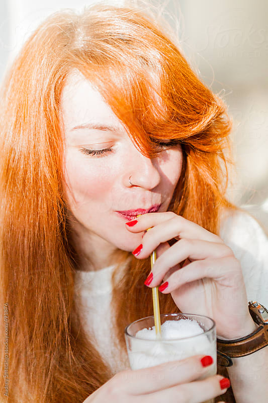 Stylish redhead woman drinking caffe latte on straw. by Audrey Shtecinjo for Stocksy United