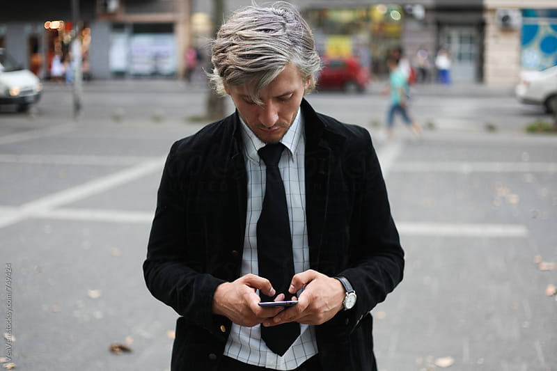 Stylish businessman browsing on his mobile phone in the street  by VeaVea for Stocksy United