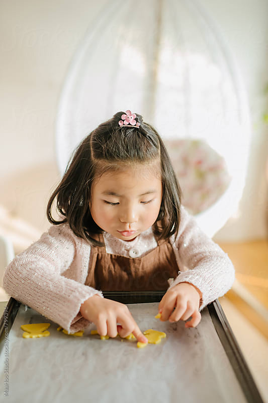 Cute little girl baking biscuits by MaaHoo Studio for Stocksy United