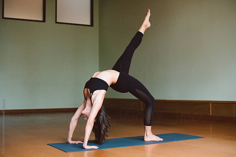 Woman doing backbend in yoga studio by Kate Daigneault for Stocksy United