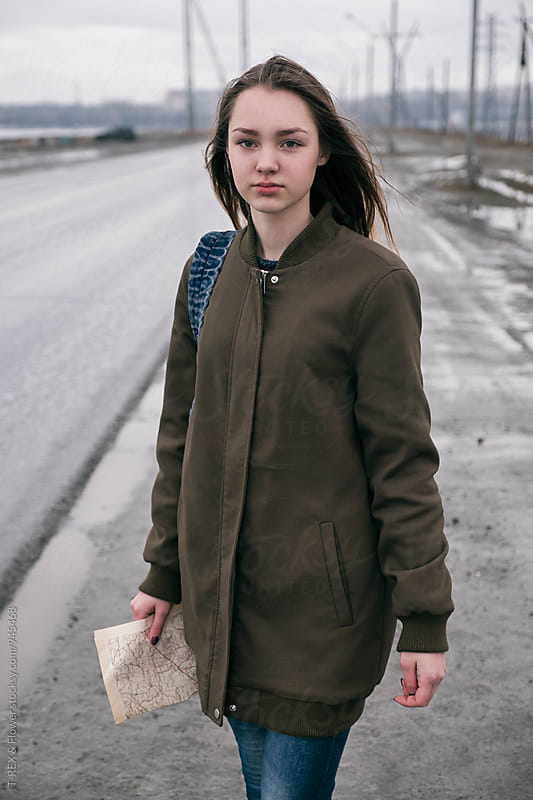 Portrait of beautiful long-haired woman with map and backpack on road by T-REX & Flower for Stocksy United