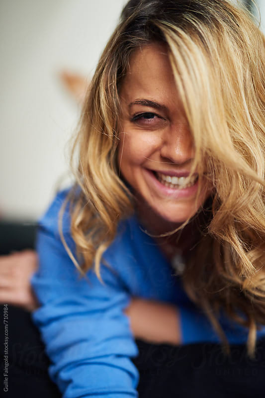 smiling blonde woman lying on bed by Guille Faingold for Stocksy United