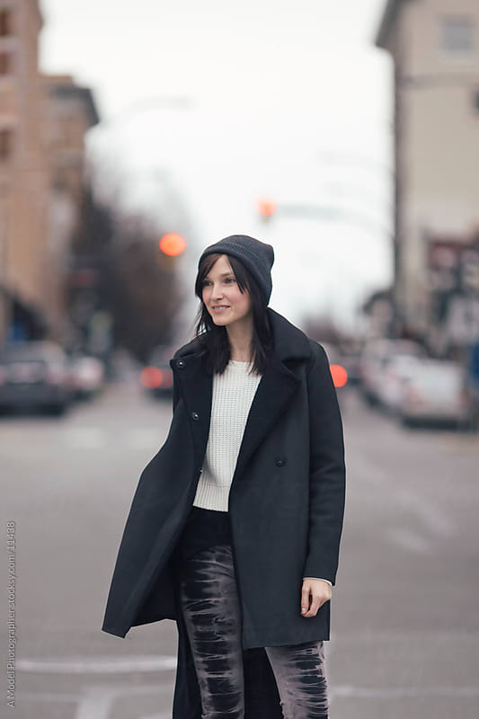 A young woman smiling on the street by Ania Boniecka for Stocksy United