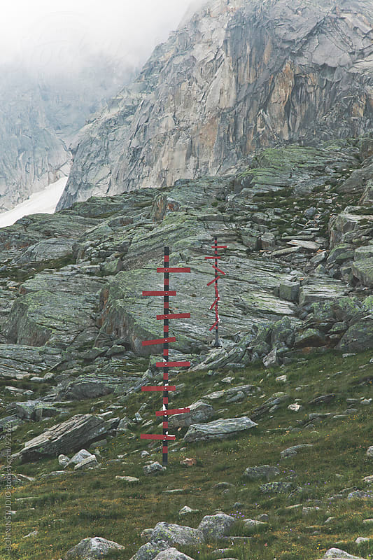Direction indicator on mountain trail, Alps, France. by BONNINSTUDIO for Stocksy United