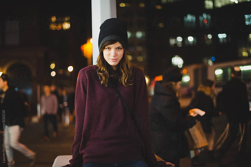Young woman in the street at night by Lauren Naefe for Stocksy United