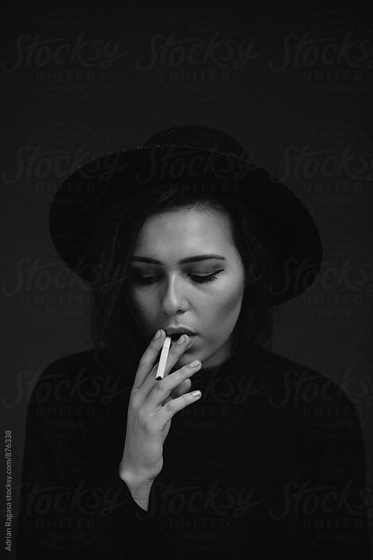 Woman Smoking with Hat by Adrian Ragasa for Stocksy United