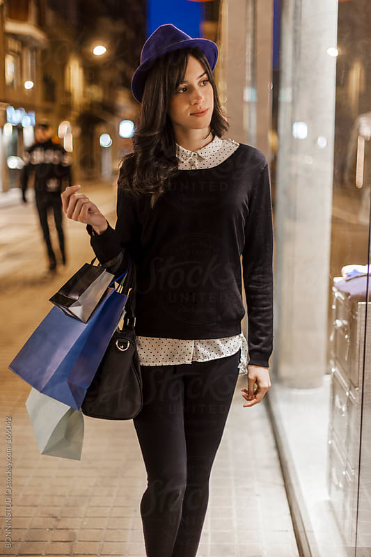 Beautiful fashion woman with many shopping bags looking a showca by BONNINSTUDIO for Stocksy United