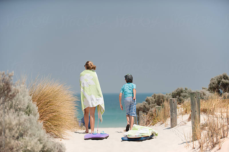 Two children walk a path through the sand dunes to the beach by Angela Lumsden for Stocksy United
