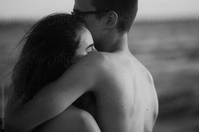 Black and white portrait of a young couple on the beach by Chelsea Victoria for Stocksy United