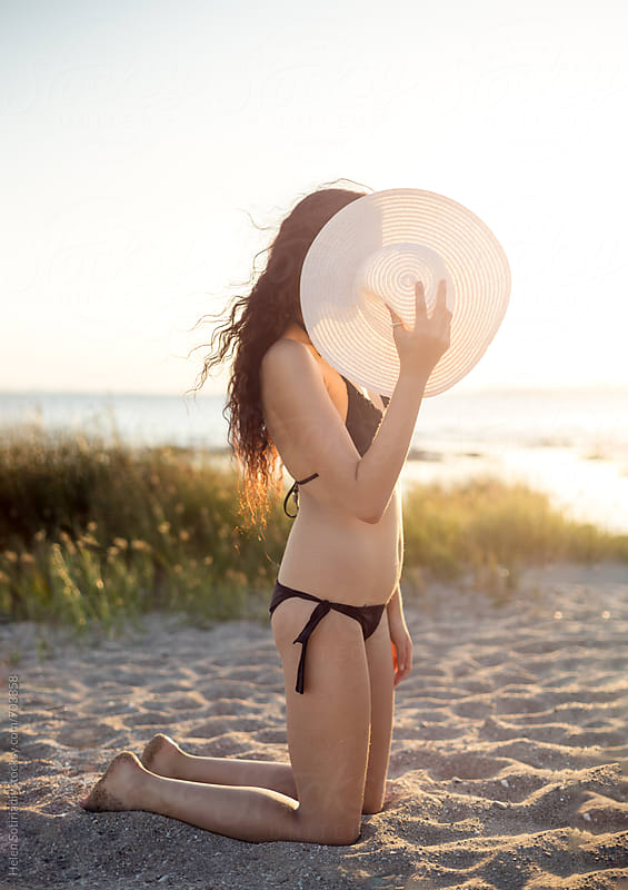 Young Woman Kneels on a Beach Hiding Behind a Hat by Helen Sotiriadis for Stocksy United
