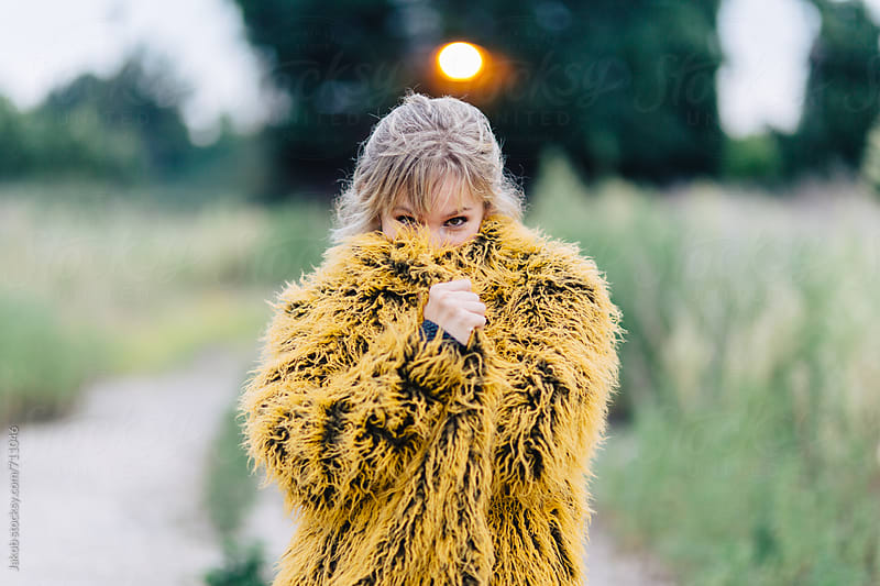 Beautiful young woman in a yellow shag coat standing outside by Jakob for Stocksy United