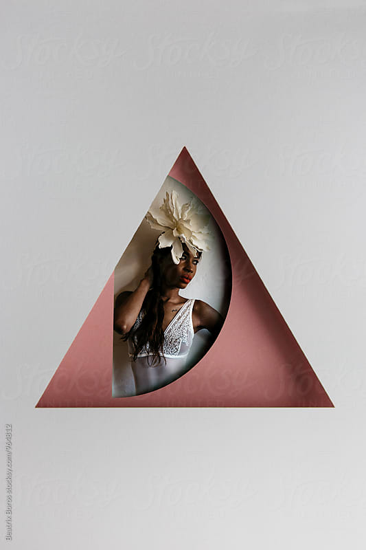Studio shot of an African American woman behind geometrical shapes by Beatrix Boros for Stocksy United