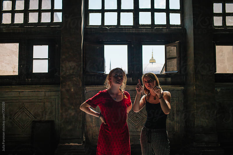 Young women discuss the interior of a historical building with windows behind them. by Julia Forsman for Stocksy United