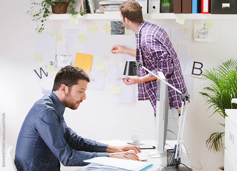Two coworkers working in the office by BONNINSTUDIO for Stocksy United